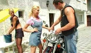 Girls are so into a biker they have a threesome in the driveway