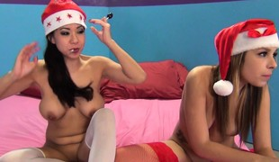Smokin' honeys Carmen Caliente and Kimmy Lee share a cock in a Christmas three-way