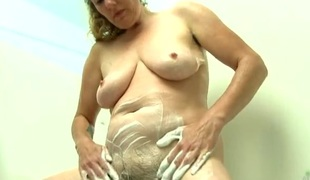 Mama soaps up her hairy slit and love melons in the tub