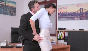 A babe is with her boss in the office and she's widening her legs for him