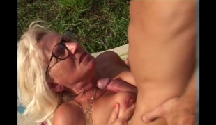 Blonde grandma acquires some cum on her glasses